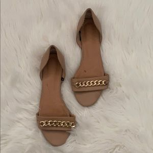 Women's tan flats with gold chain detail.
